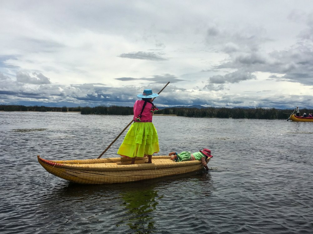 A young woman poles through the shallow waters of Lake Titicaca. Although the lake is nearly 1,000 feet deep, the Uros live close to the shoreline where the reeds grow and the lake is no more than 10 feet deep. (TNS/Thomas Curwen)