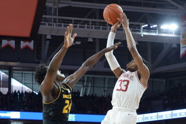 Arkansas guard Jimmy Whitt Jr. (33) takes as shot Friday, Feb. 21, 2020, over Missouri forward Kobe Brown during the second half in Bud Walton Arena in Fayetteville.