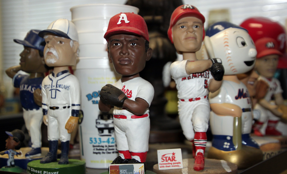 "The jersey on the bobblehead at left reads ""Field of Dreams."" At center is a bobblehead from the Arkansas Travelers; at right, this bobblehead is from Memphis's minor league team, which is affiliated with the St. Louis Cardinals. These three are part of the collection of baseball fan and mathematics professor Fred Worth.