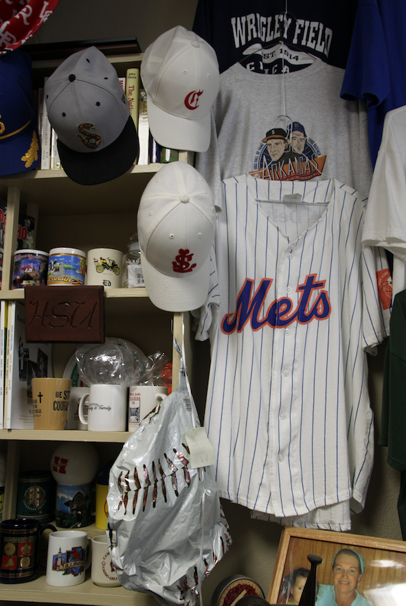 An assortment of baseball team jerseys, caps, mugs and more pack the shelves in Fred Worth's office. Worth, who visits the gravesites of baseball players, has written about his unusual hobbybut has yet to find a publisher.