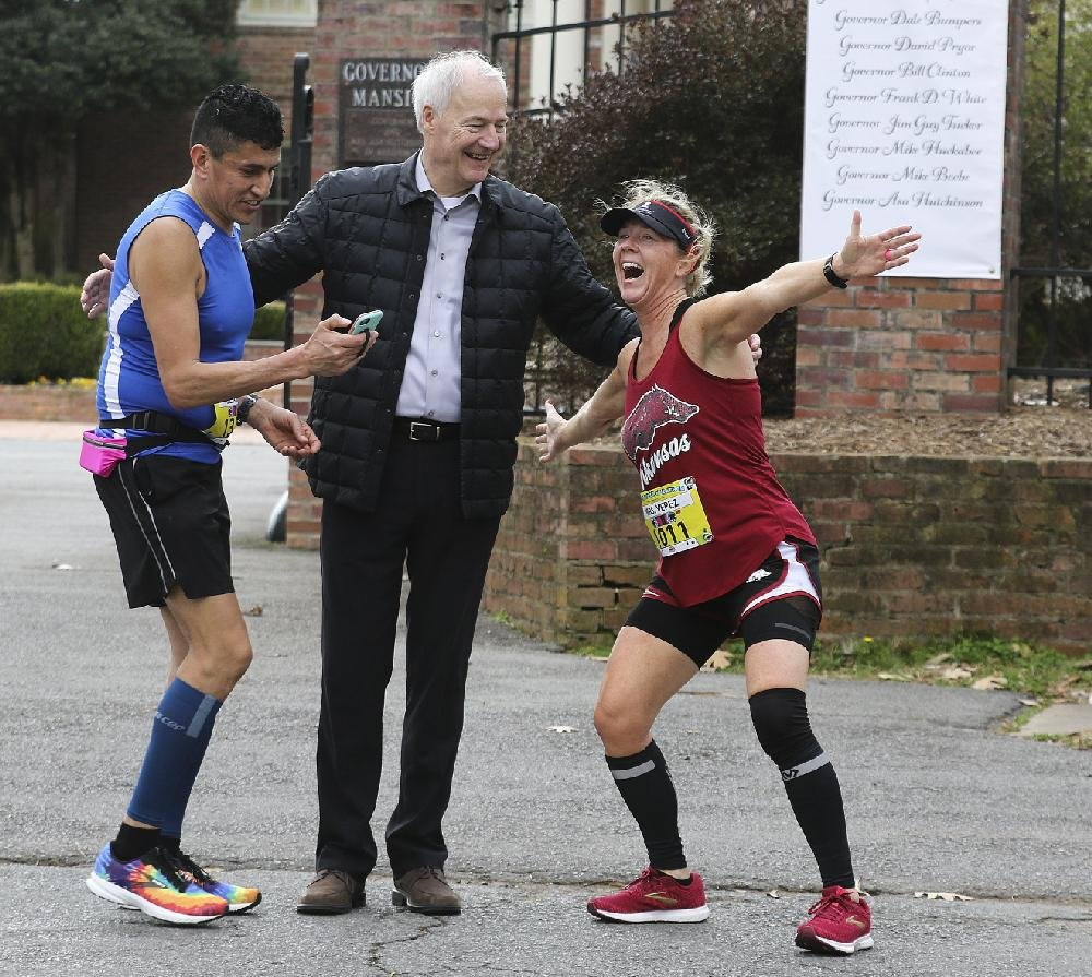 Gov. Asa Hutchinson takes a selfie with runners Alejandro Yepez (left) and Andrea Peet outside the Governor's Mansion during the Little Rock Marathon. See more photos at arkansasonline.com/marathon/