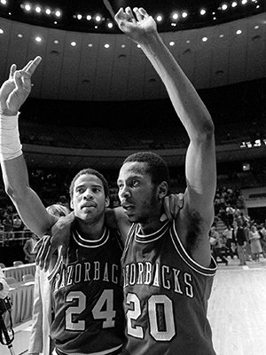 Two tired Arkansas teammates, guard U.S. Reed (24) and guard Darrell Walker (20) raise arms in victory March 15,1981 after Reed sank a final second shot from mid-court to beat Louisville 74-73 in second round of NCAA tournament in Austin. Walker, who returned to the starting lineup after an 11 game absence, led Arkansas, scoring 23 points in the stunning victory. (AP Photo)