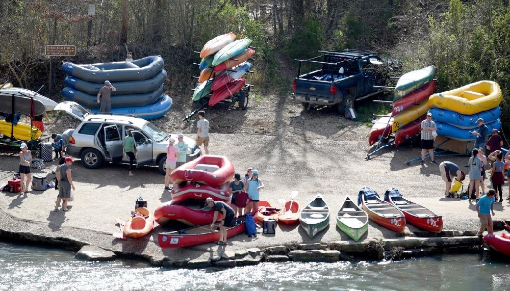 From the low water bridge in Ponca in Newton County, outfitters and private boaters prepare Thursday to set off on the Buffalo River. (NWA Democrat-Gazette/David Gottschalk)
