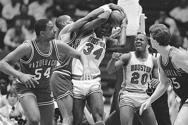 Houston's Akeem Abdul Olajuwon (34) is fouled by Arkansas' Alvin Robertson (21) in the first half of the championship game at the Southwest Conference Tournament in Houston on March 11, 1984. (AP Photo)