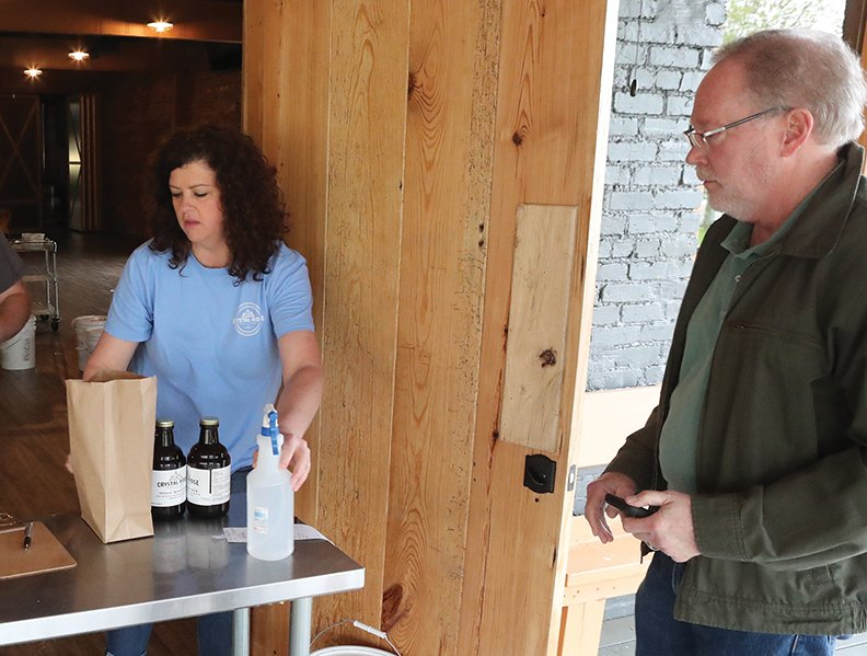 Co-owner Mary Bradley, left, fills an order of Crystal Ridge Distillery's hand sanitizer for customer David Hamilton on Friday. - Photo by Richard Rasmussen of The Sentinel-Record