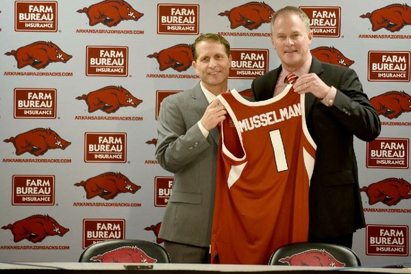NWA Democrat-Gazette/DAVID GOTTSCHALK Eric Musselman (left) receives a jersey from Athletic Director Hunter Yurachekat a press conference after his introduction as the new head coach of men's basketball at the University of Arkansas by Yurachek Monday, April 8, 2019 in Bud Walton Arena on the campus in Fayetteville. During the previous four seasons, Musselman coached the University of Nevada in Reno to a 110-34 record.