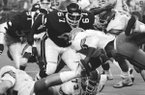 Arkansas defensive lineman Richard Richardson (67) closes in on Florida running back Lorenzo Hampton (7) stretches for a yard in the fourth quarter of the Bluebonnet Bowl game in Houston on Friday, Dec. 31, 1982. (AP Photo)