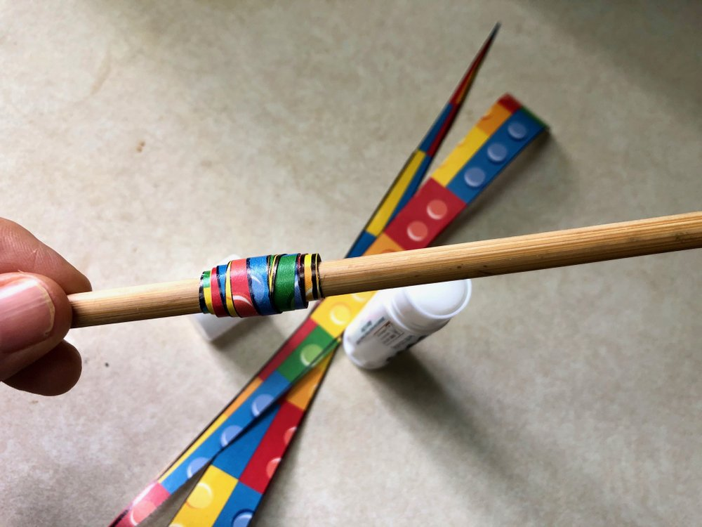 Long thin paper triangles wrapped around a chopstick and glued become paper beads in this craft project. (Arkansas Democrat-Gazette/Celia Storey)