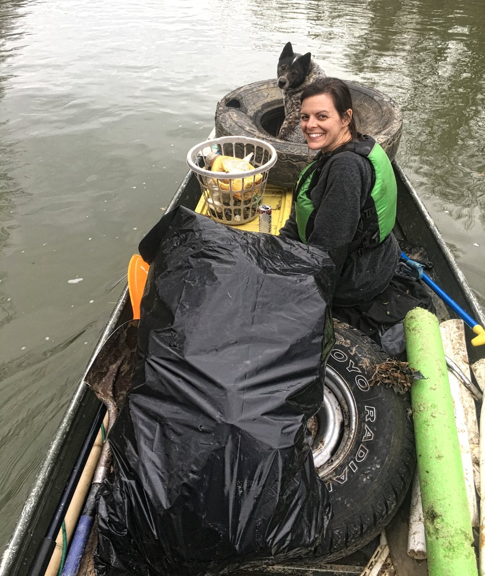 Tonya Sacomani is almost crowded out of the boat by trash she and her family hauled from the Saline River. (Special to the Democrat-Gazette/Michael and Tonya Sacomani)