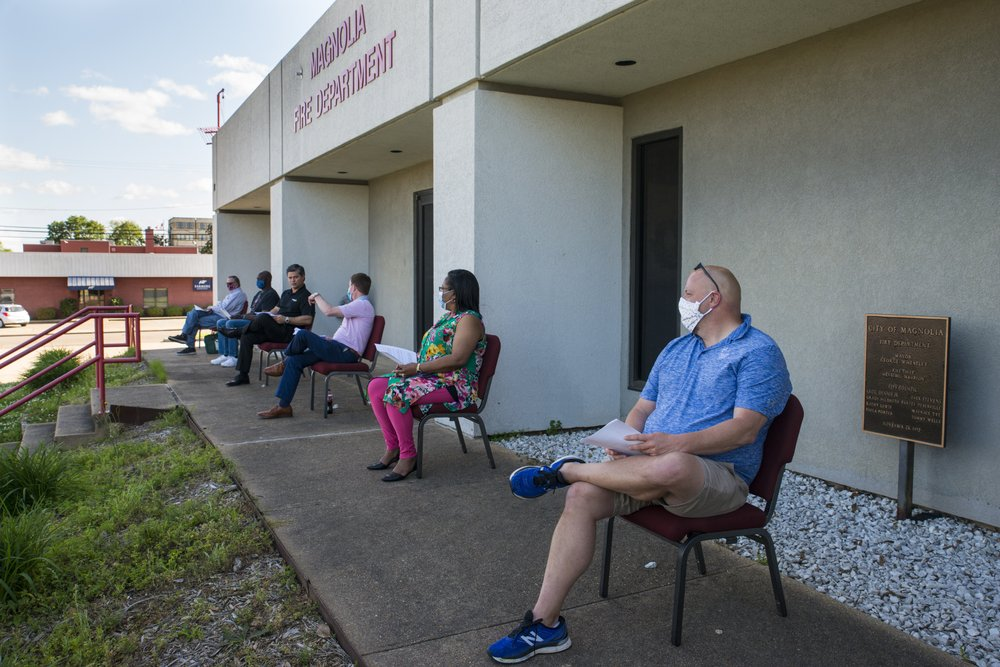 Magnolia City Council members, most of whom were masked, sit outside of their normal meeting chambers on Thursday, April 23, during a specially-called meeting.