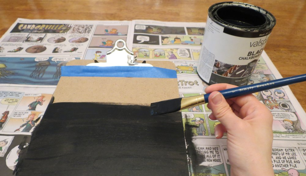 2. Open the chalkboard paint and mix according to paint instructions. Paint the clipboard below the tape, moving in the same direction to create a smooth surface. (You can apply a second paint coat, if you like.) Wash the paintbrush in a sink. After 10 minutes, gently reposition the clipboard on the newspaper to avoid any sticking. Let it dry for 24 hours. (Photo for The Washington Post by Kris Coronado)
