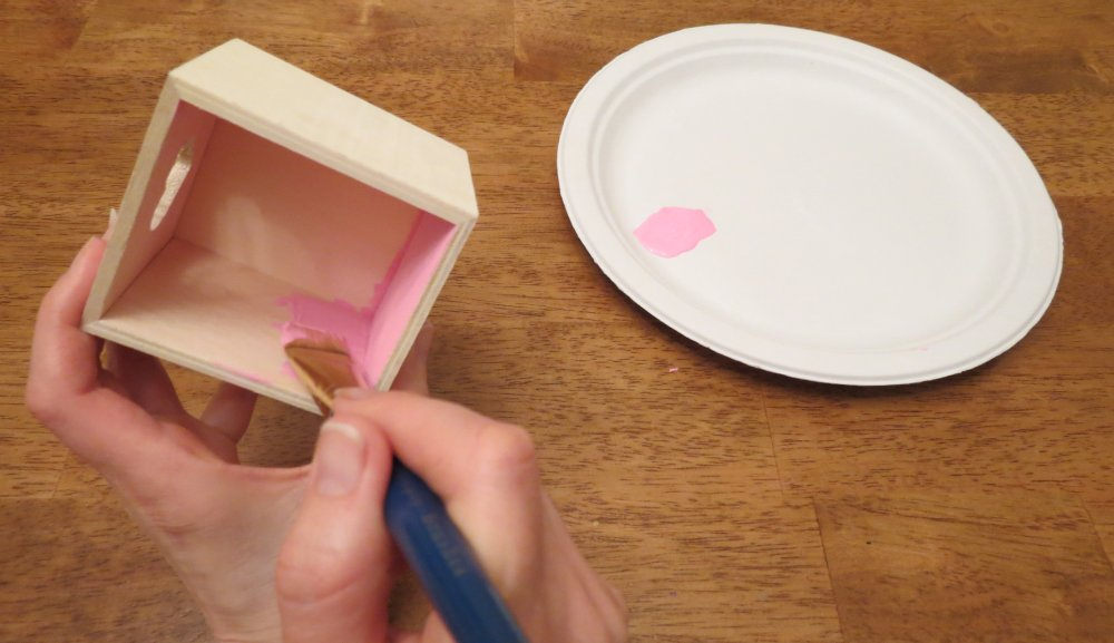 3. As the clipboard dries, squirt a quarter-size amount of one acrylic paint color on the paper plate. Use this color to paint the inside of the wooden box, using more paint as needed. When the inside is finished, rinse the paintbrush and paint the outside with the second color. Place the box on the newspaper to dry for five minutes. (Photo for The Washington Post by Kris Coronado)