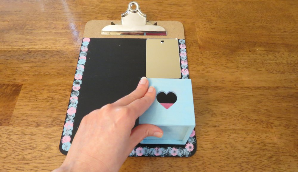 5. Keep the clipboard flat and glue the mirror to the top right of the chalkboard. (The glue doesnմ dry right away, so donմ tilt the clipboard!) Glue the painted box to the bottom right with the opening facing the top of the clipboard. (Photo for The Washington Post by Kris Coronado)
