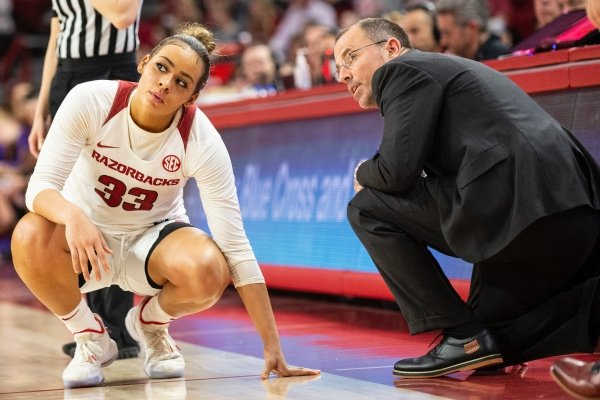 Arkansas guard Chelsea Dungee (33) and assistant coach Todd Schaefer talking along the sideline as the Razorbacks play LSU at Bud Walton Arena in Fayetteville on Sunday, March 1, 2020.