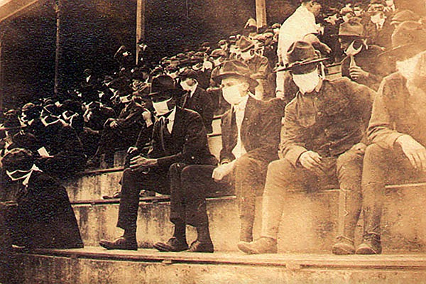This photo provided by Georgia Tech alumnus Andy McNeil shows a Georgia Tech home game during the 1918 college football season. The photo was taken by Georgia Tech student Thomas Carter, who would receive a degree in Mechanical Engineering. The 102-year-old photo could provide a snapshot of sports once live games resume: Fans packed in a campus stadium in the midst of a pandemic wearing masks with a smidge of social distance between them on concrete seats. (Thomas Carter via AP)