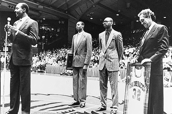Sidney Moncrief (front) speaks to the Barnhill Arena crowd while Marvin Delph (left), Ron Brewer (center) and Eddie Sutton listen behind him on March 3, 1990, in Fayetteville.