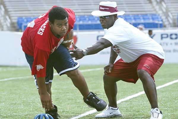 Former Arkansas running back Oscar Malon (right) works with Malcomb Watson of Brinkley while coaching at the Brandon Burlsworth Football Camp on Saturday, June 5, 2004, at War Memorial Stadium in Little Rock. The Burlsworth camps have been hosted each year since 2000 in Harrison and Little Rock, but will be moved to a virtual setting this year because of the covid-19 outbreak.