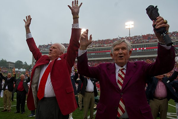 Johnny Majors (right) and Frank Broyles participate in a Hog Call prior to an Arkansas game against Alabama on Oct. 11, 2014, in Fayetteville. The men were on the field for a ceremony celebrating the 50th anniversary of the Razorbacks' 1964 national championship team. Majors was an assistant coach for Broyles for four seasons from 1964-67.