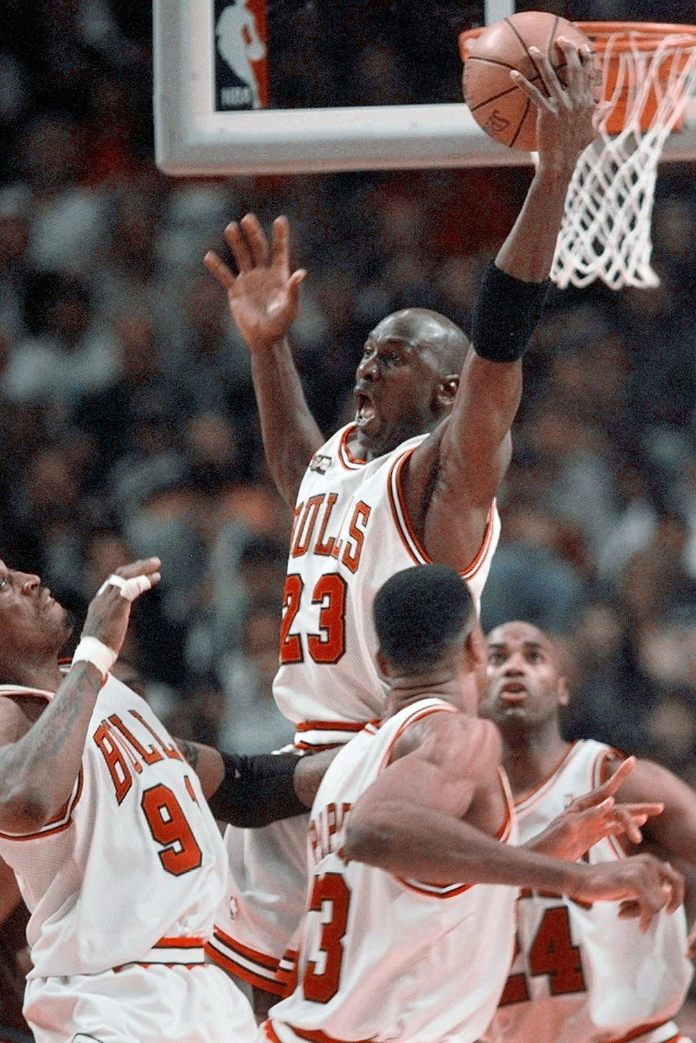 """In this June 10, 1998, file photo, Chicago Bulls' Michael Jordan reaches high above teammates for a rebound against the Utah Jazz in Game 4 in the NBA Finals in Chicago. Jordan described his final NBA championship season with the Chicago Bulls as a """"trying year. We were all trying to enjoy that year knowing it was coming to an end,"""" Jordan told Good Morning America on April 16.  (AP)"""