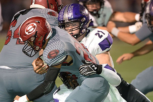 Springdale running back Gilberto Dominguez (left) is brought down Friday, Oct. 25, 2019, by Fayetteville defender Kaiden Turner (21) during the first half of play at Jarrell Williams Bulldog Stadium in Springdale.
