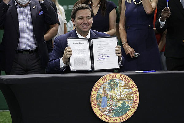 Florida Gov. Ron DeSantis holds up a just signed bill which would allow college athletes in the state to earn money from endorsement deals, Friday, June 12, 2020, at the University of Miami in Coral Gables, Fla. (AP Photo/Lynne Sladky)