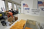 In this April 14, 2020 photo, Nadette Cheney picks up a box of printed ballots as others work on preparing mail-in ballots at the Lancaster County Election Committee offices in Lincoln, Neb. (AP Photo/Nati Harnik)