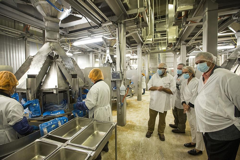 Visitors get a look at packaging work Tuesday during a tour of the Tyson plant in Rogers. (NWA Democrat-Gazette/Ben Goff)