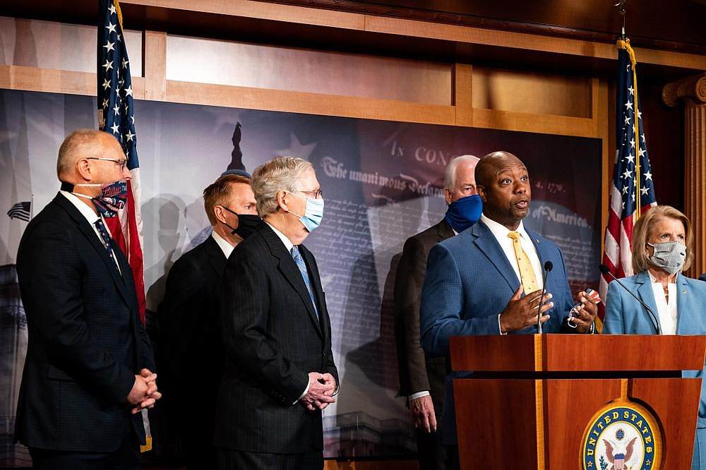 """Sen. Tim Scott, with Senate Majority Leader Mitch McConnell and other GOP senators around him, said at a news conference Wednesday that there is a lot of overlap in House and GOP approaches to police overhauls, adding that """"most of us want about 70% of the same change."""" (The New York Times/Anna Moneymaker)"""