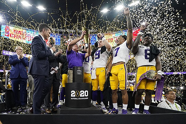In this Jan. 13, 2020, file photo, LSU head coach Ed Orgeron holds the trophy after the team's victory over Clemson in an NCAA College Football Playoff national championship game in New Orleans. LSU has begun asking a number of football players to self-quarantine in the past week because of instances in which some players tested positive for covid-19 after social interactions outside of the Tigers' training facility. (AP Photo/David J. Phillip, File)