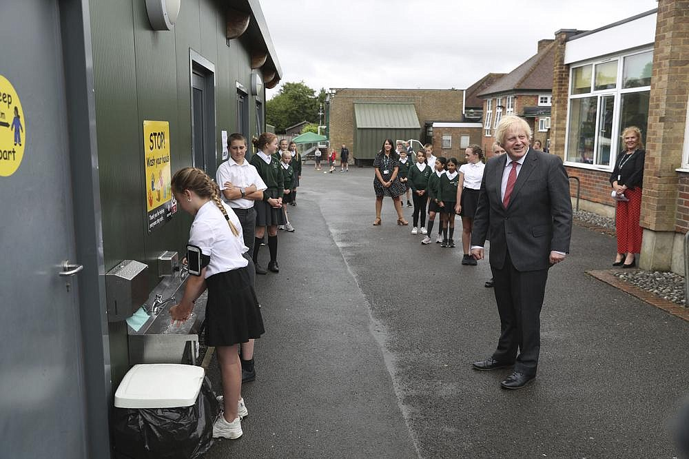 British Prime Minister Boris Johnson waits in line to wash his hands Friday at a playground at Bovingdon Primary School in Bovingdon, Hemel Hempstead, England. Britain lowered its coronavirus threat level on Friday, saying its national outbreak is getting under control. (AP/Steve Parsons)