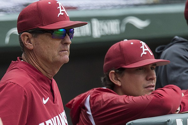 Arkansas coach Dave Van Horn (left) and student assistant Harrison Heffley watch from the dugout during a game against LSU on Saturday, May 11, 2019, in Fayetteville.