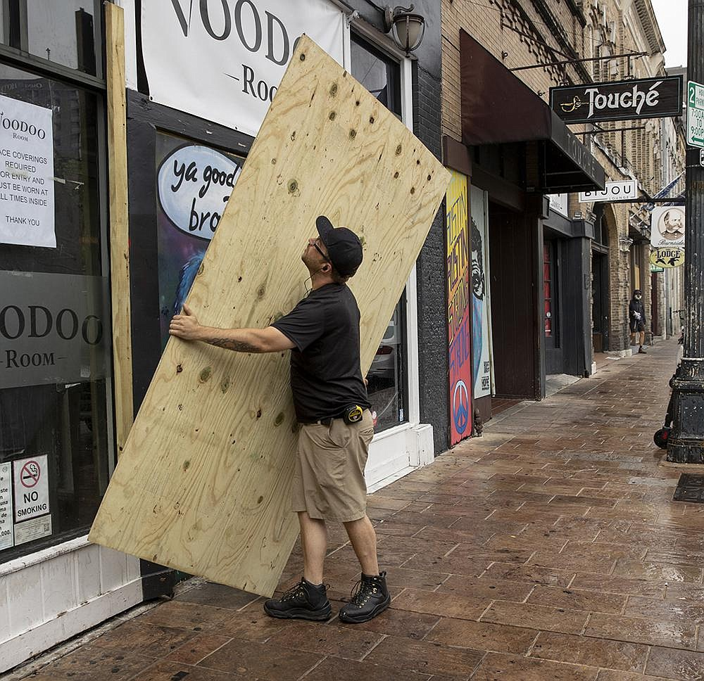 A man boards up the Voodoo Room on East Sixth Street in Austin on Friday after Texas Gov. Greg Abbott ordered bars in Texas to close because of the coronavirus. (AP/Austin American-Statesman/Jay Janner)