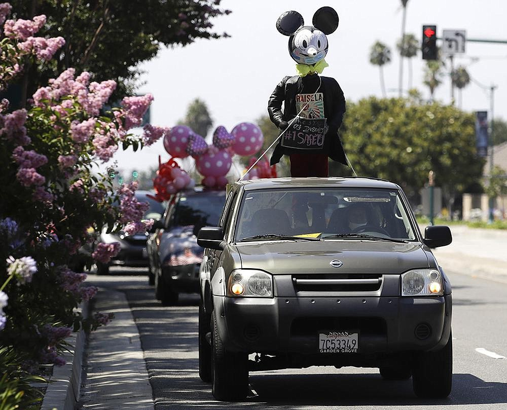 Disney employees parade past Disneyland on Saturday in Anaheim, Calif., during a protest to demand a safe reopening with regular coronavirus testing, stricter cleaning protocols and higher staffing levels. Disney had originally proposed reopening on July 17 but announced last week that it would wait.