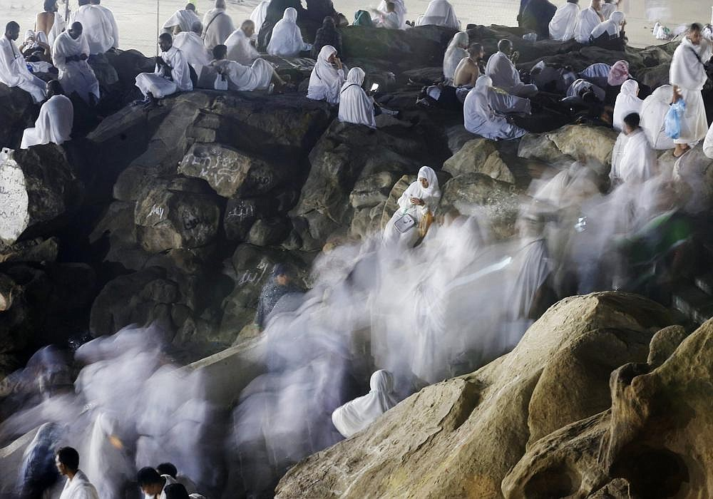 In this August file photo taken with low shutter speed, Muslim pilgrims make their way up a rocky hill known as Mountain of Mercy, on the Plain of Arafat, during the annual hajj pilgrimage, ahead of sunrise near the holy city of Mecca, Saudi Arabia. This year's hajj will be all but canceled, as Saudi Arabia is in the midst of one of the largest coronavirus outbreaks in the Middle East.