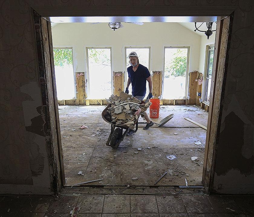Ryan Bennett tears out Sheetrock at his grandmother's house on Willow Beach Road in North Little Rock on June 10, 2019, after the house was flooded the previous week.