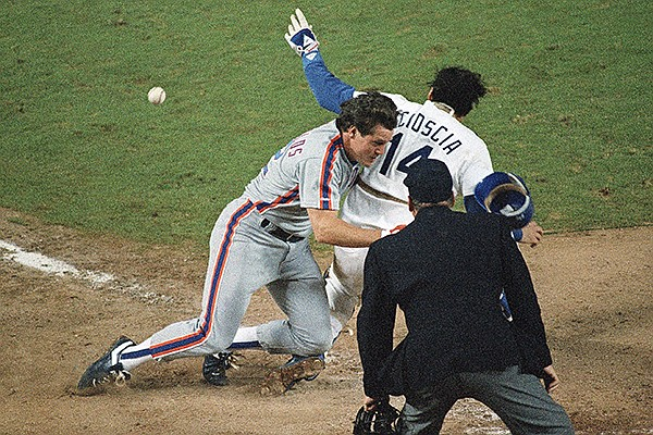New York Mets Kevin McReynolds, left, is blocked by Los Angeles Dodgers catcher Mike Scioscia (14) as he makes his way to home plate during ninth inning action in Game 1 of the National League Championship Series in Los Angeles, Oct. 5, 1988. Scioscia did not catch the ball and McReynolds scored on the play to lift the Mets past the Dodgers, 3-2. Umpire Harry Wendelstedt watches the play. (AP Photo/Lennox McLendon)