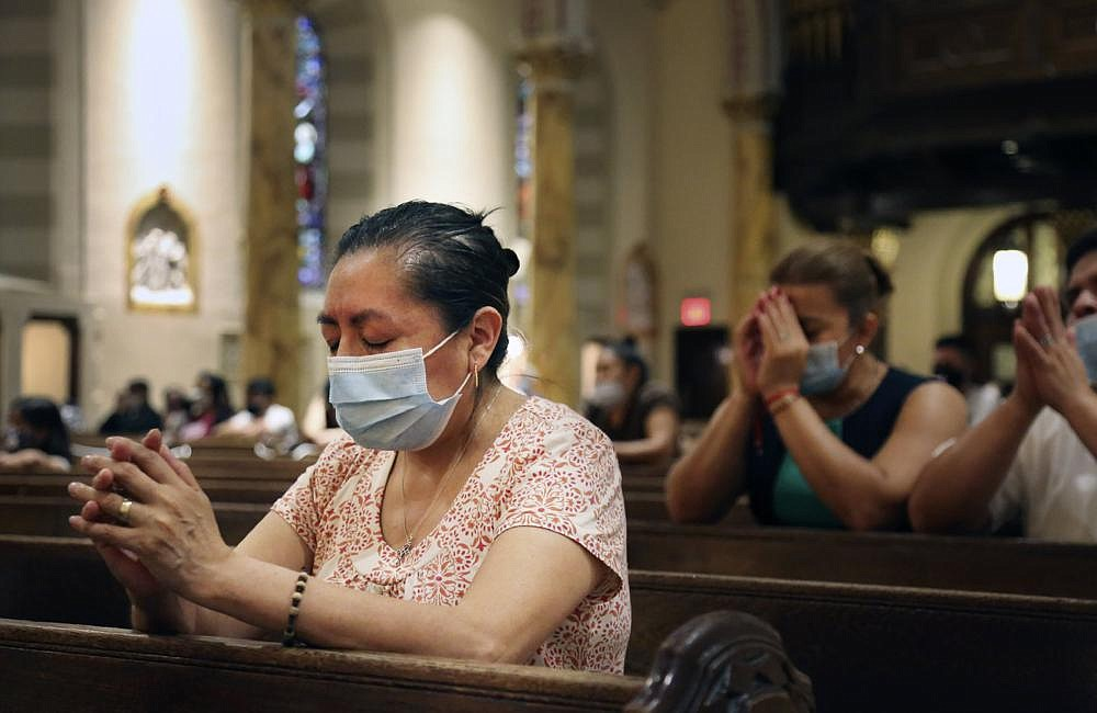 Claudia Balderas, 51, prays for her brother, who died from covid-19 in May, on Monday, while attending the fi rst in-person Mass in almost four months at the Queens, N.Y., Saint Bartholomew Roman Catholic Church.
