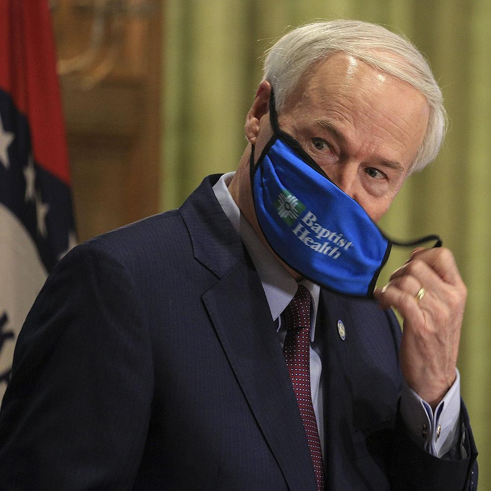 """Gov. Asa Hutchinson removes his mask before Thursday's briefing. """"This is not about arresting anyone,"""" Hutchinson said of the mask mandate. """"It's about education, but it's also about a penalty, and it's a consequence, and so they can be issued a citation."""" More photos at arkansasonline.com/717governor/. (Arkansas Democrat-Gazette/Staton Breidenthal)"""