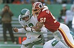 Philadelphia Eagles quarterback Randal Cunningham, left, fumbles the ball as he gets tackled by Washington Redskins linebacker Ravin Caldwell during the first quarter of NFL action from Veterans Stadium in Philadelphia, Dec. 4, 1988. (AP Photo/Rusty Kennedy)