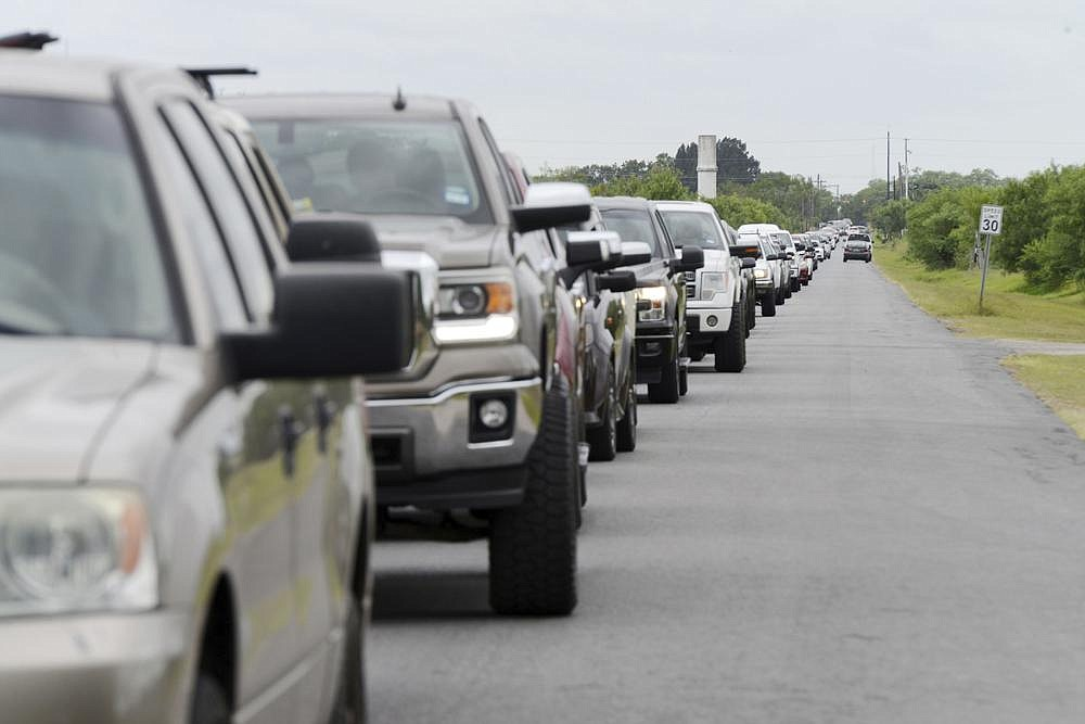 Hundreds of motorists wait in line for sandbags in Brownsville, Texas, to get ready for expected torrential rainfall from Hurricane Hanna, which swept ashore Saturday as a Category 1 storm.