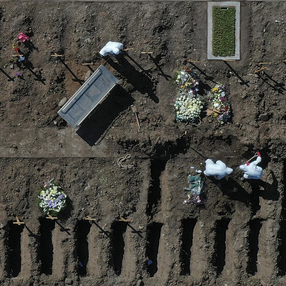 Cemetery workers prepare graves Saturday in a section for coronavirus victims at the Flores cemetery in Buenos Aires, Argentina. More photos at arkansasonline.com/726covid/. (AP/Gustavo Garello)
