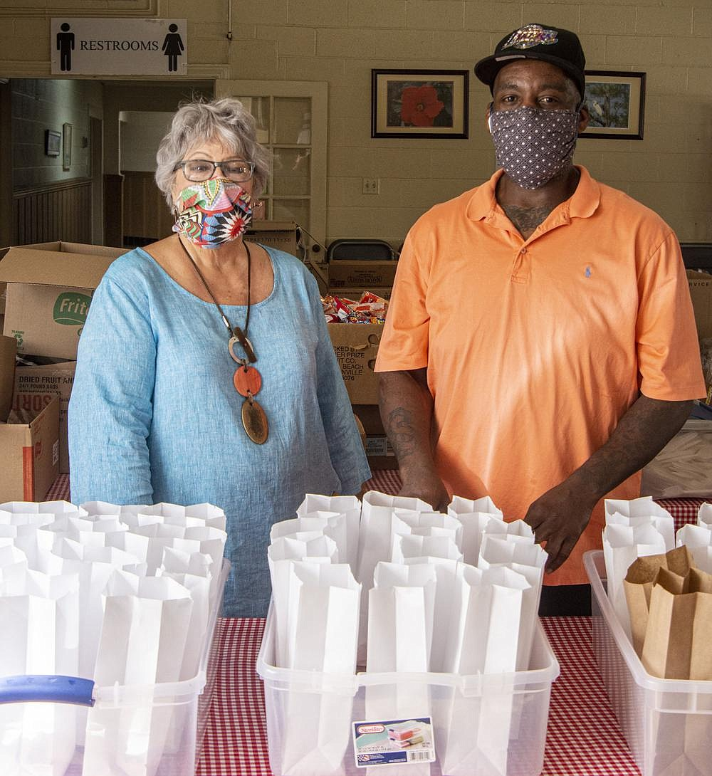 """As board chairwoman for the Stewpot, Nancy Howell has steered the change — necessitated by the covid-19 pandemic — in getting midday meals to the hungry in downtown Little Rock. Instead of diners coming in to eat, they receive sack lunches distributed by employee Ed Brown (right). Howell says Stewpot ensures that meals are not just nutritious, but fun. """"We're not going to make them 'eat their turnips,'"""" she says. (Arkansas Democrat-Gazette/Cary Jenkins)"""