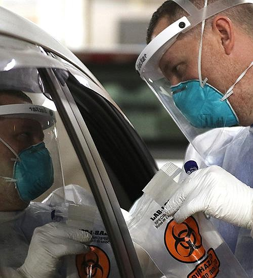 Andrew Becker talks to a motorist Friday after administering a covid-19 test at the University of Arkansas for Medical Sciences drive-thru testing site. (Arkansas Democrat-Gazette/Thomas Metthe)