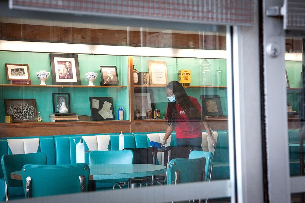 An employee sanitizes a table Wednesday at a diner in the Fondren neighborhood of Jackson, Miss. The state reported 1,505 new coronavirus cases and 20 more deaths on Wednesday, putting the total at 55,804 cases and 1,563 deaths.