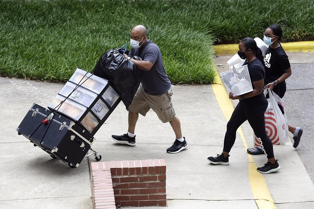 College students begin moving in for the fall semester Friday at N.C. State University in Raleigh, where student returns were staggered over 10 days and volunteers wearing masks and face shields greeted the returning scholars. More photos at arkansasonline.com/81covid/