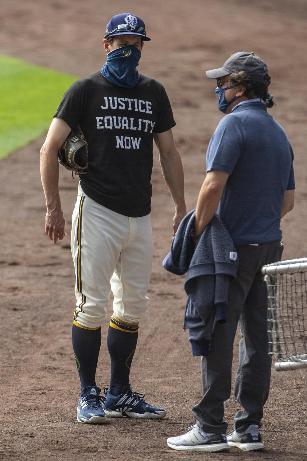 Milwaukee Brewers owner Mark Attanasio (right) talks to Manager Craig Counsell on Friday after it was announced that the home opener was postponed because two St. Louis Cardinals players tested positive for the coronavirus. (AP/Morry Gash)