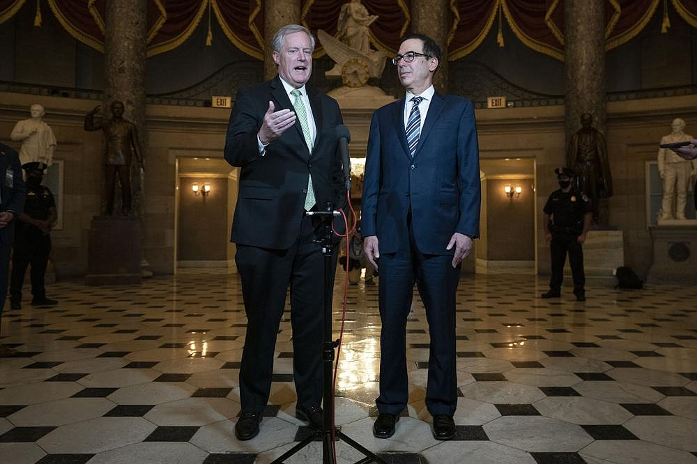 """White House Chief of Staff Mark Meadows (left) and Treasury Secretary Steven Mnuchin criticized Democratic congressional negotiators Thursday. Meadows said a compromise on a stimulus package """"has to have a dollar sign in front of it"""" for talks to go forward. (AP/Carolyn Kaster)"""