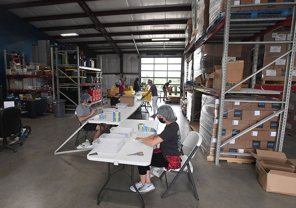 Employees along with some restaurant workers make meal packs July 29 at The Pack Shack in