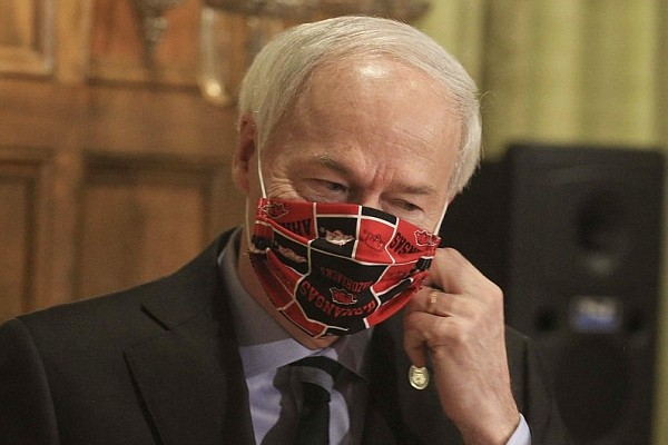 In this April 27, 2020 file photo, Gov. Asa Hutchinson takes off his Arkansas Razorbacks facemask as he arrives for the daily coronavirus briefing at the state Capitol in Little Rock.