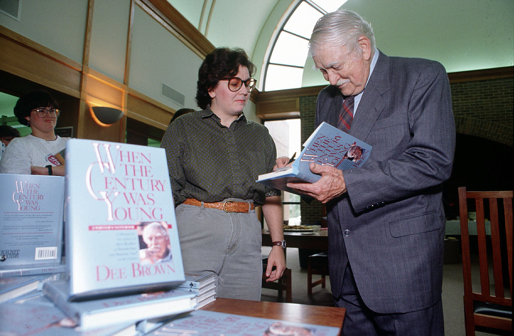 Dee Brown autographs a copy of his book at a 1993 signing party. (Democrat-Gazette file photo)